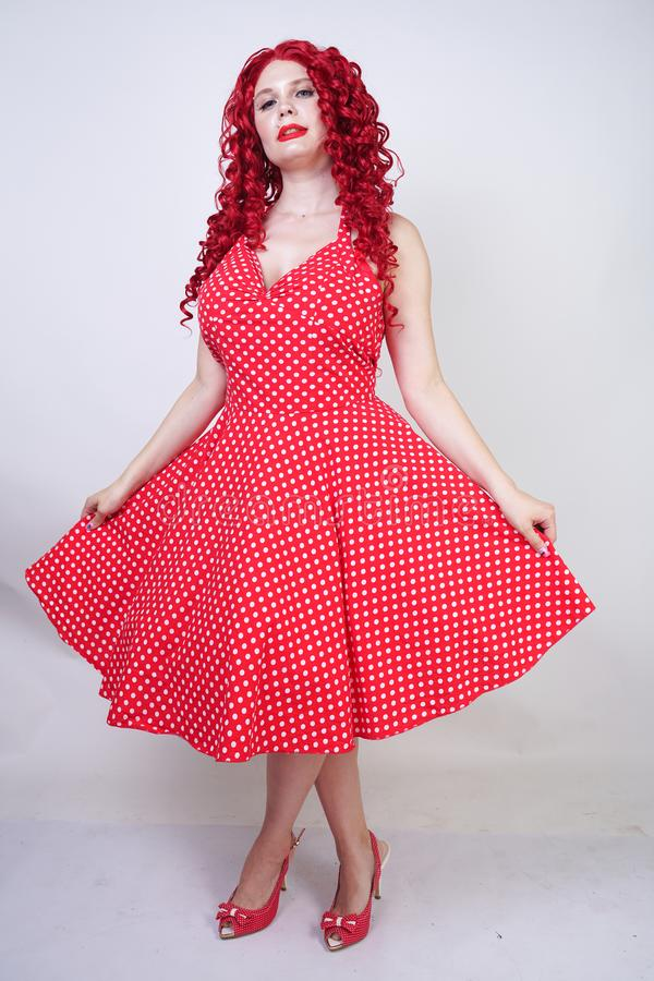 Plus krullende vrouw van het grootte de rode haar met curvy lichaam die retro stip mooie kleding dragen en zich op witte studio a royalty-vrije stock afbeeldingen