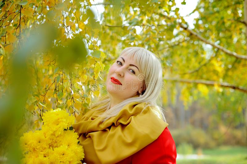 Plus size blonde woman with a bouquet of yellow flowers outdoors. She stands against a background of trees with yellow stock photos