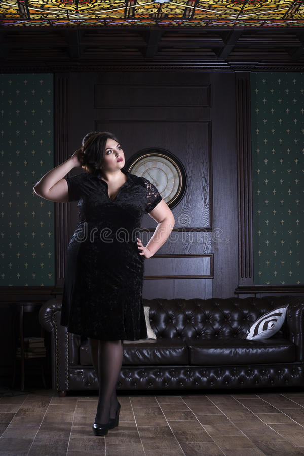 Plus size fashion model in black evening dress, fat woman on luxury interior, overweight female body, full length portrait royalty free stock photos