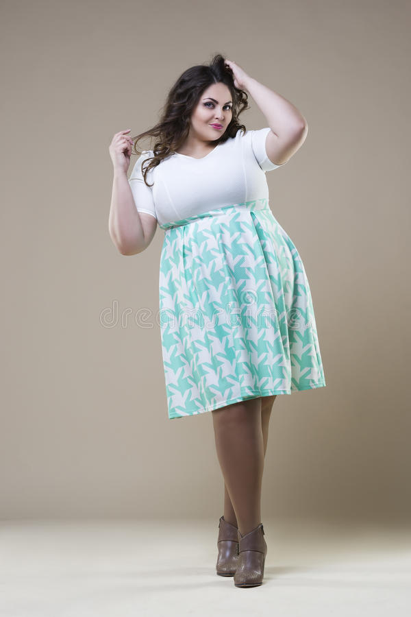Plus size fashion model in casual clothes, fat woman on studio background, overweight female body. Plus size fashion model in casual clothes, fat woman on beige royalty free stock photo