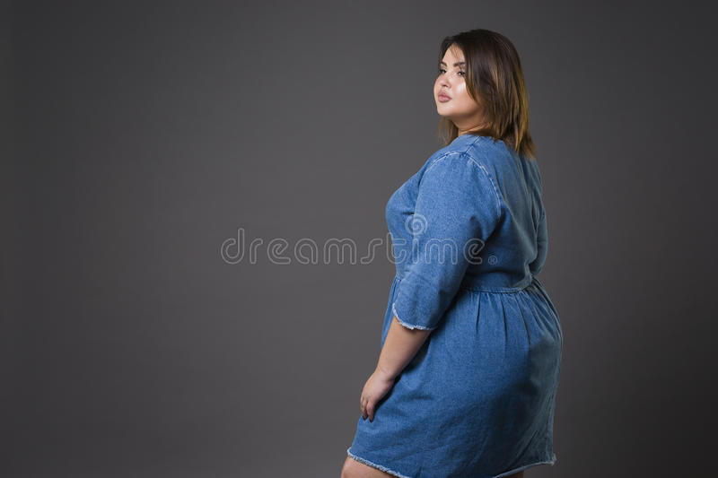 Plus size fashion model in casual jeans clothes, fat woman on gray background, overweight female body stock photos
