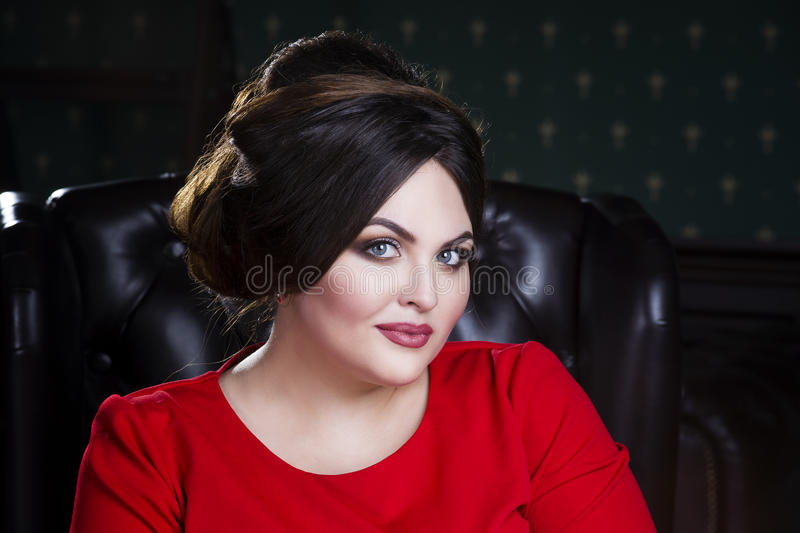 Plus size fashion model in red dress with professional make-up and hairstyle stock photos