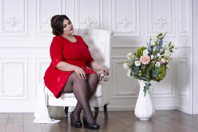 Plus size fashion model in red evening dress, fat woman on luxury interior, overweight female body, full length portrait stock image