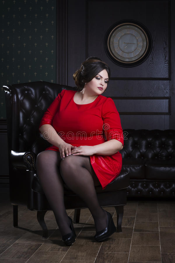 Plus size fashion model in red evening dress, fat woman on luxury interior, overweight female body, full length portrait. Professional make-up and hairstyle stock photos
