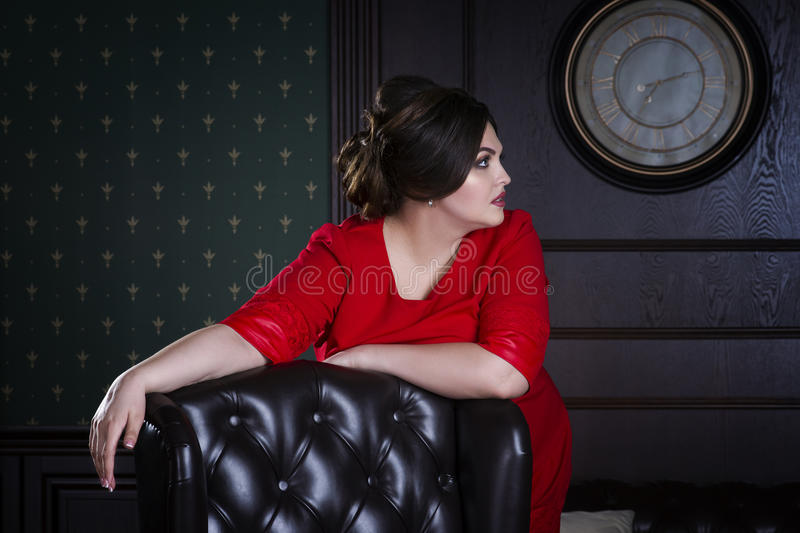 Plus size fashion model in red evening dress, fat woman on luxury interior, overweight female body royalty free stock photos