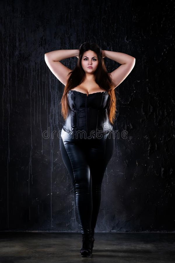 Plus size fashion model in clothes, fat woman on black background, overweight female body royalty free stock images