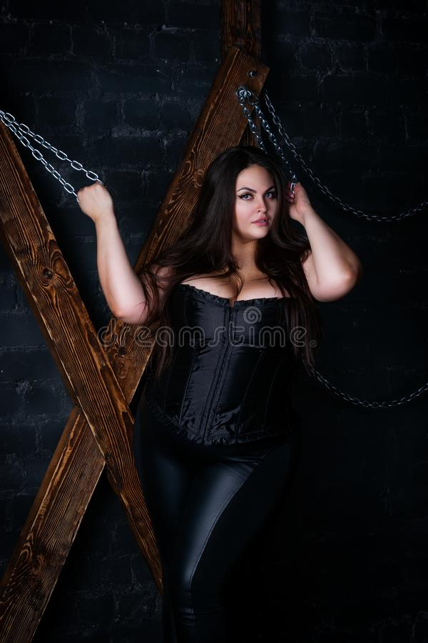 Plus size fashion model tied with chains to a wooden cross, fat woman in sexy clothes. Love game and bdsm concept royalty free stock image