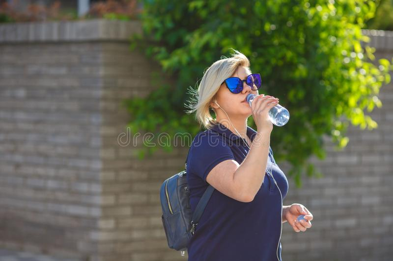 Plus size girl drinking water from a bottle royalty free stock image
