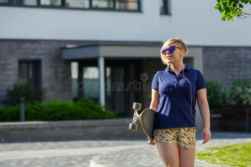 Plus size girl with a longboard walking stock image