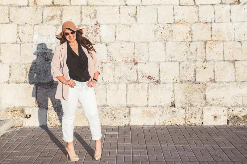Plus size model wearing fashion clothes in city street. Young stylish woman wearing neutral blazer and hat walking on the city street in evening. Casual fashion stock photography