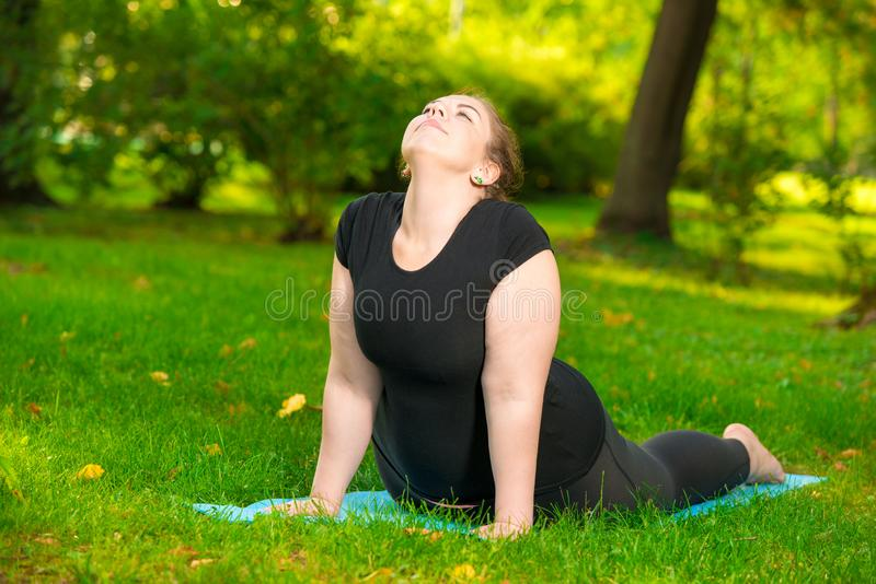 plus size sports woman in park performs stretching exercises stock photos