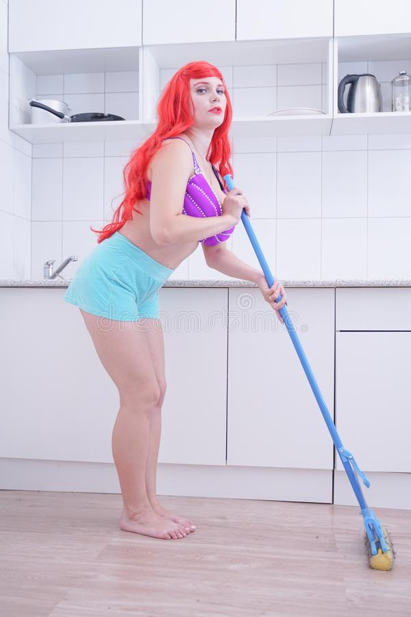 Plus size woman cleaning home, posing with mop and having fun. Plus size woman cleaning home kitchen with mop. Housework, chores concept royalty free stock photo