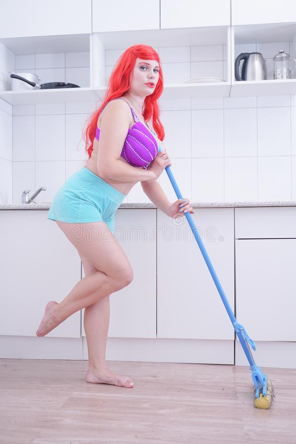 Plus size woman cleaning home, posing with mop and having fun. Plus size woman cleaning home kitchen with mop. Housework, chores concept royalty free stock photography
