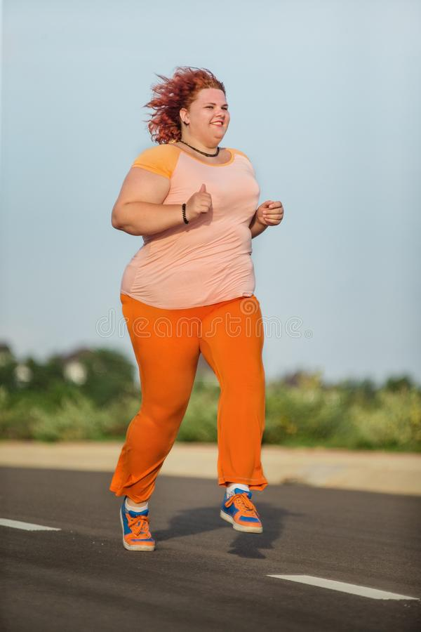 Beautiful young fat woman is runing stock images