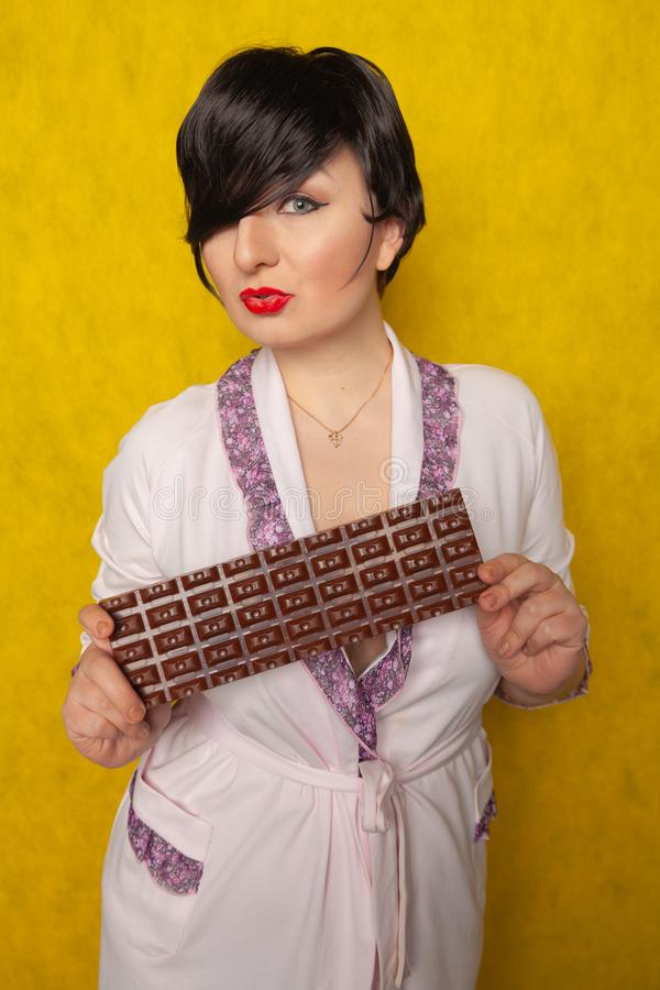 Plus size woman stands in a pink Bathrobe and holding in her hands a huge bar of chocolate on yellow background. Alone royalty free stock images
