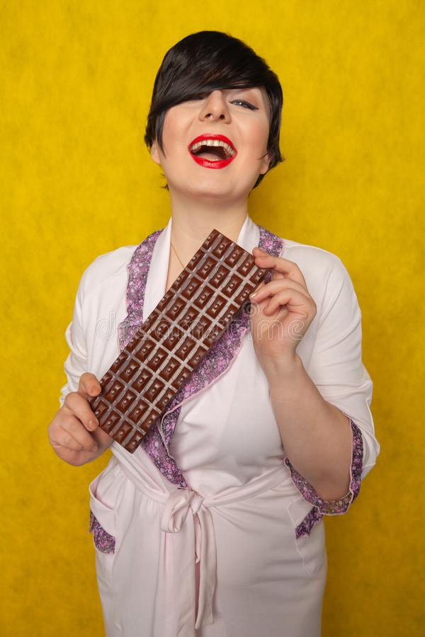 Plus size woman stands in a pink Bathrobe and holding in her hands a huge bar of chocolate on yellow background. Alone royalty free stock photos