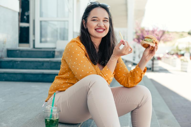 Plus size woman walking down the city and eating burger royalty free stock images