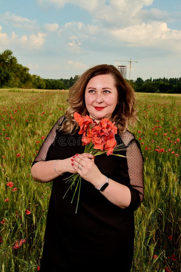 Plus storleksanpassad kvinna i en svart klänning på ett fält av grönt vete och lösa vallmo Överviktig fet kvinna arkivbilder