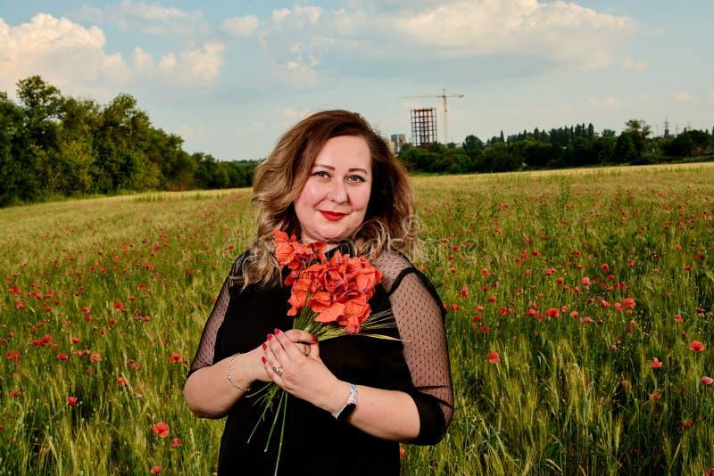 Plus storleksanpassad kvinna i en svart klänning på ett fält av grönt vete och lösa vallmo Överviktig fet kvinna arkivbild