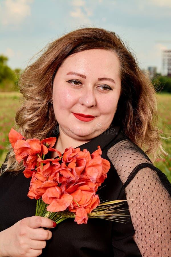 Plus storleksanpassad kvinna i en svart klänning på ett fält av grönt vete och lösa vallmo Överviktig fet kvinna royaltyfri foto