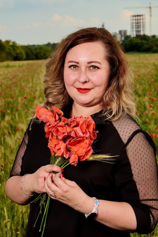 Plus storleksanpassad kvinna i en svart klänning på ett fält av grönt vete och lösa vallmo Överviktig fet kvinna fotografering för bildbyråer