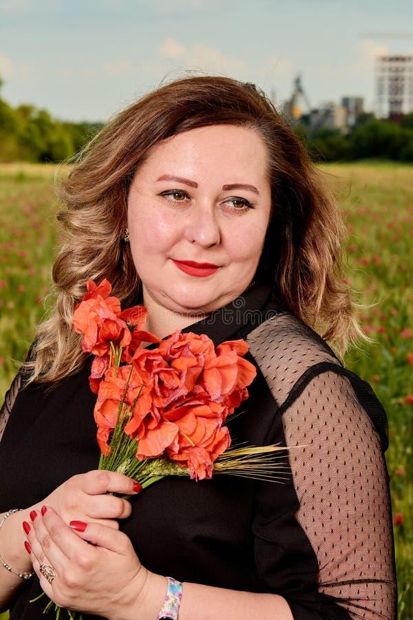 Plus storleksanpassad kvinna i en svart klänning på ett fält av grönt vete och lösa vallmo Överviktig fet kvinna arkivfoton
