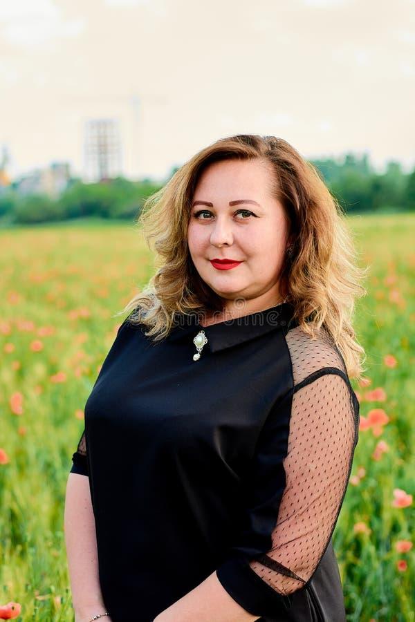 Plus storleksanpassad kvinna i en svart klänning på ett fält av grönt vete och lösa vallmo Överviktig fet kvinna royaltyfri fotografi