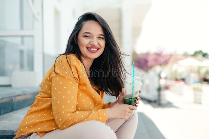 Plus wielkościowa kobieta pije szpinaka smoothie podczas gdy chodzący miasto ulicę obraz royalty free