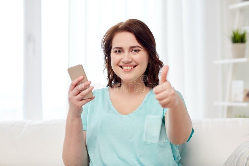 Plus wielkościowa kobieta z smartphone pokazuje aprobaty fotografia royalty free