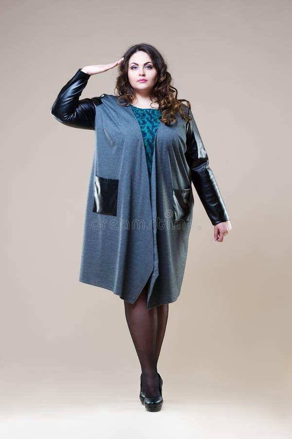 Plus wielkościowy moda model salutuje w przypadkowych ubraniach, gruba kobieta na beżowym pracownianym tle, z nadwagą żeński ciał fotografia royalty free