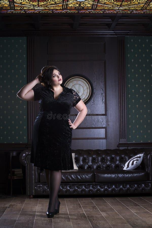 Plus wielkościowy moda model w czarnej wieczór sukni, gruba kobieta na luksusowym wnętrzu, z nadwagą żeński ciało, pełny długość  zdjęcia royalty free
