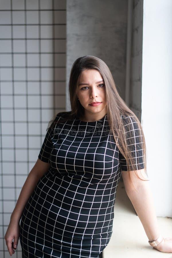 Plus wielkościowy moda model w przypadkowych ubraniach, kobieta na pracownianym tle, z nadwagą żeński ciało obrazy stock