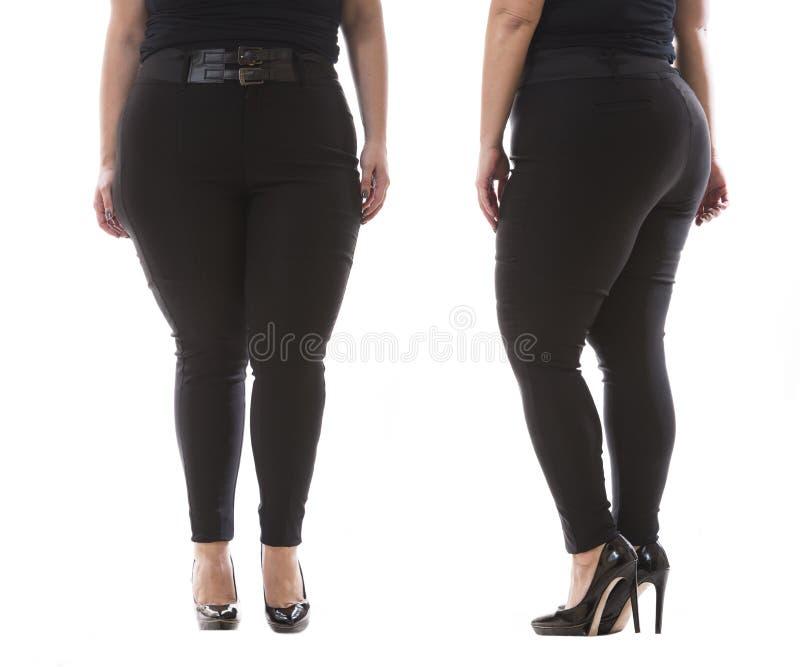 Plus zwarte vrouwelijke klassieke broek van de grootte de modelslijtage XXL met leerriem en hoge hielen op wit royalty-vrije stock foto's