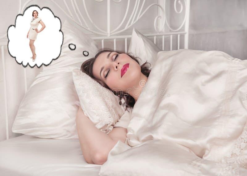 Plusgrößenfrau, die über dünnes selbst schläft und träumt lizenzfreies stockfoto