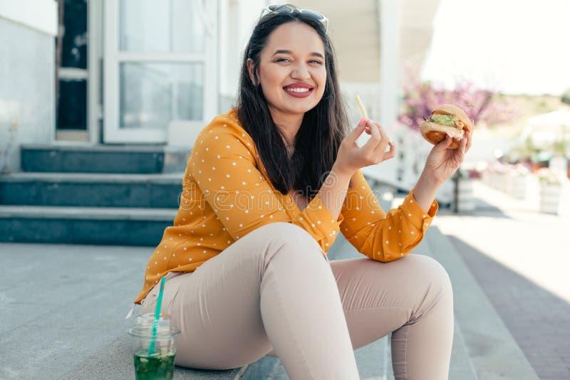 Plusgrößenfrau, die hinunter die Stadt geht und Burger isst lizenzfreie stockbilder