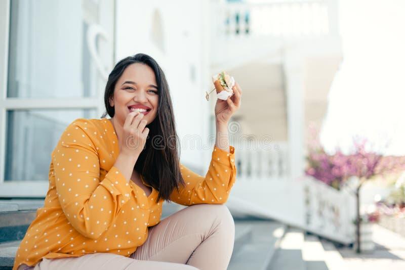 Plusgrößenfrau, die hinunter die Stadt geht und Burger isst lizenzfreie stockfotografie