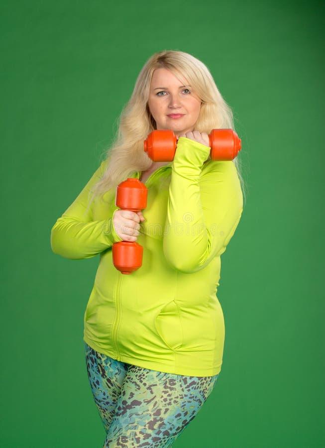 Plusgrößenfrau, die oben muscules mit Dummköpfen auf Grün zurück pumpt stockfotos