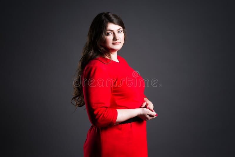 Plusgrößenmode-modell im roten Kleid, fette Frau auf grauem Hintergrund, überladener weiblicher Körper stockfoto