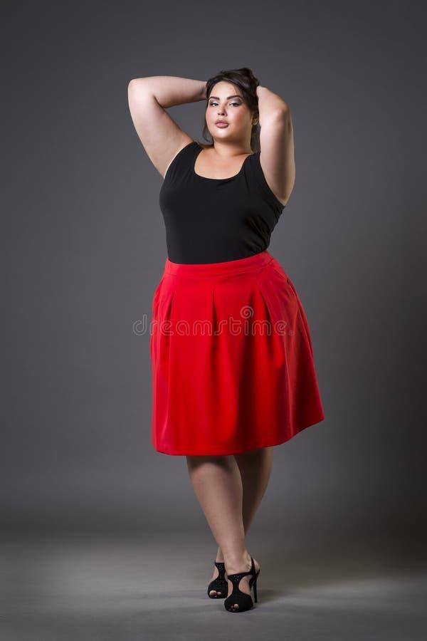 Plusgrößenmode-modell im roten Rock, fette Frau auf grauem Hintergrund, überladener weiblicher Körper stockfotos