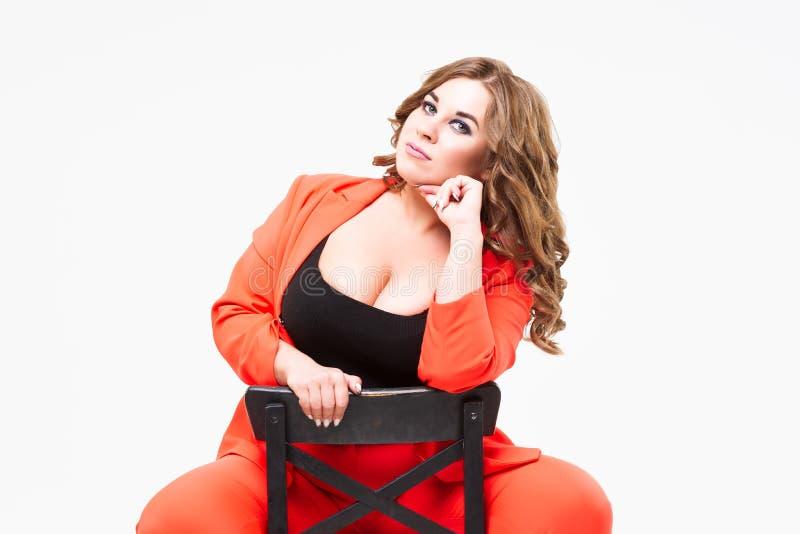 Plusgr??enmodell mit der gro?en Brust und tiefer decollete, fetter Frau auf wei?em Hintergrund im orange Pantsuit, positives Konz stockfotografie