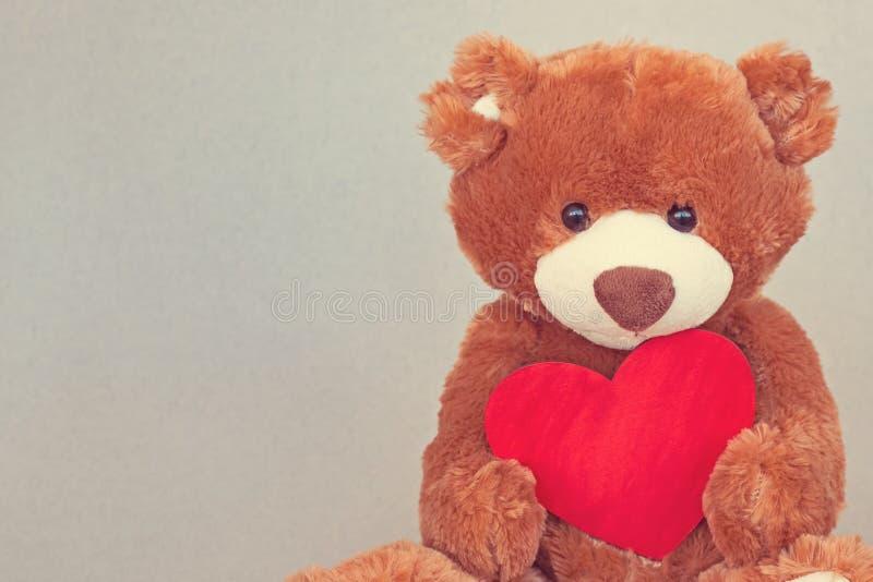 Plush cute toy Teddy Bear holding a red heart stock photos