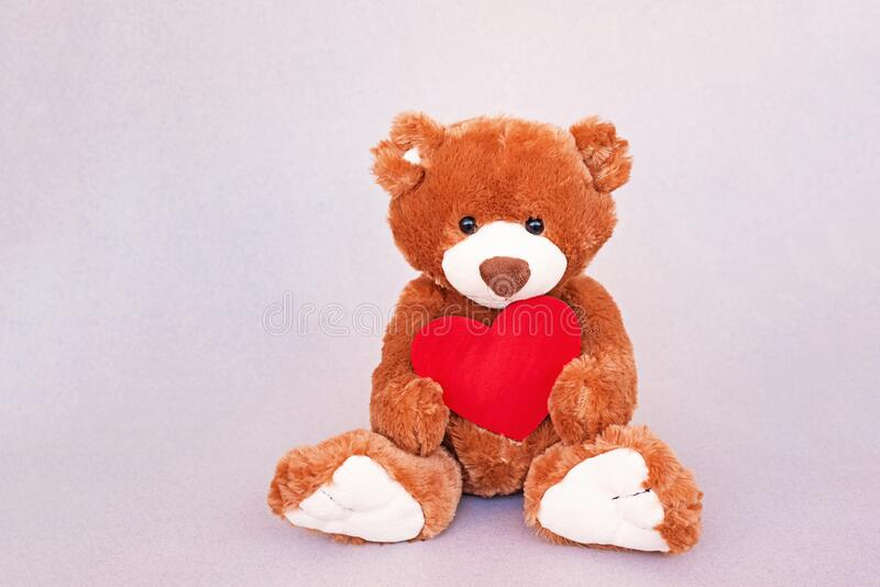 Plush cute toy Teddy Bear holding a red heart stock images