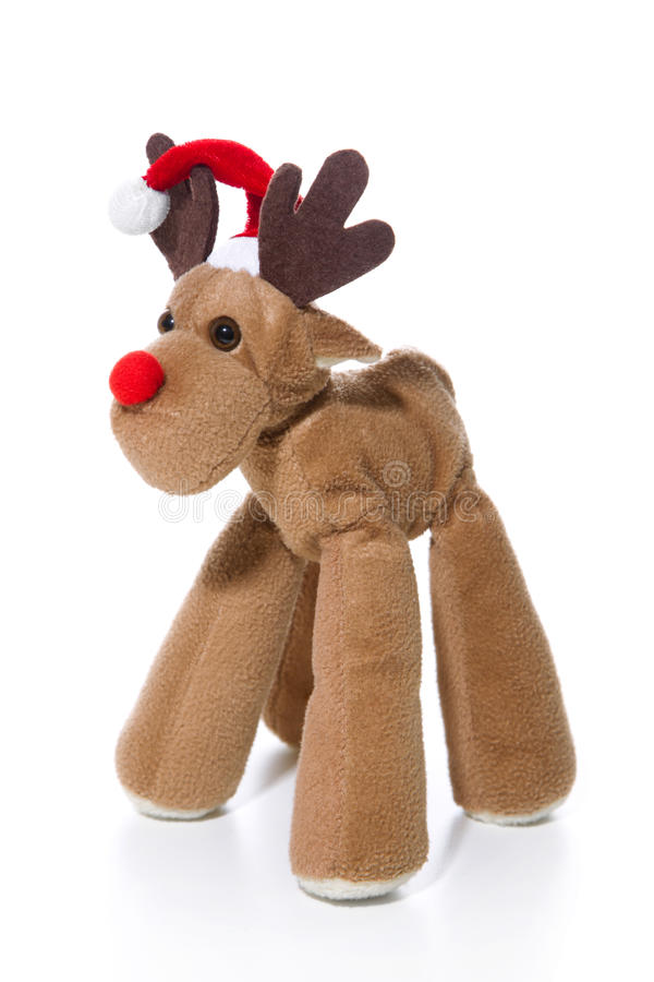 Plush reindeer with Santa hat isolated with a red christmas hat. Decoration: Plush reindeer with Santa hat isolated with a red christmas hat royalty free stock photography