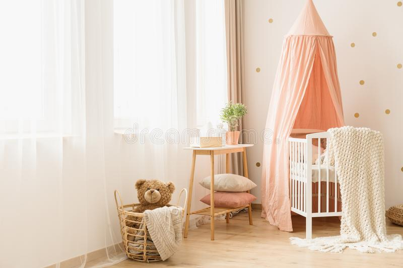 Pastel cozy baby`s bedroom interior. Plush toy in basket near a white crib with pastel canopy in cozy baby`s bedroom interior royalty free stock photo
