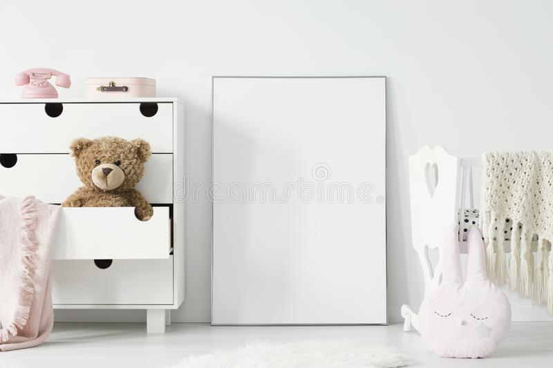 Plush toy in cabinet next to poster with mockup and cradle in ba. By`s bedroom interior. Real photo. Place for your graphic royalty free stock image