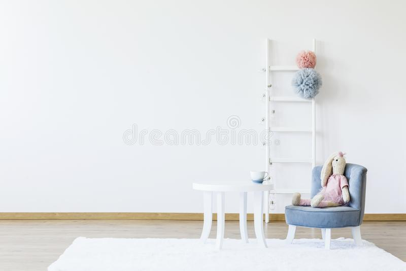Plush toy on grey chair at white table in minimal child`s room i stock images
