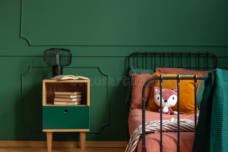 Plush toy and pillows on single metal bed next to wooden nightstand with books and industrial lamp royalty free stock photo