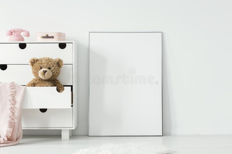 Plush toy and pink blanket in cabinet next to empty white poster royalty free stock photos