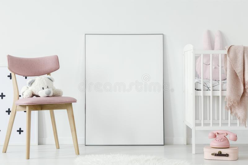 Plush toy on pink chair next to poster with mockup in baby`s roo royalty free stock photo