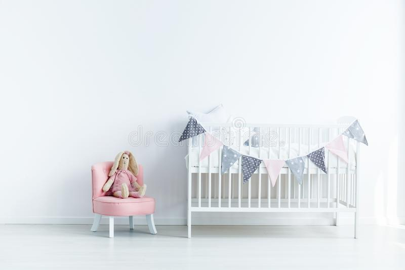 Plush toy on pink chair next to white crib in white baby`s bedro. Om interior. Real photo royalty free stock images